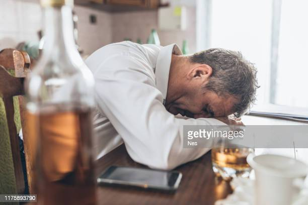 an elderly man abuses alcohol - drunk stock pictures, royalty-free photos & images