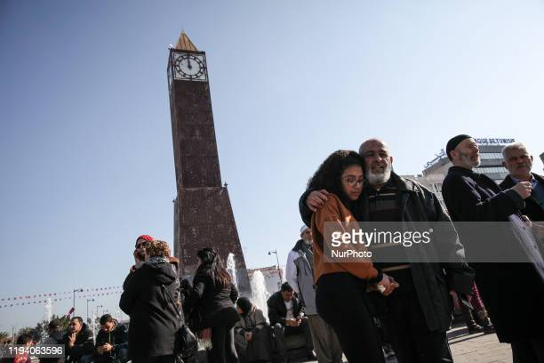 An elderly man and a female teenager are seen next to the clock tower of avenue Habib Bourguiba in the capital Tunis as they attend the celebrations...