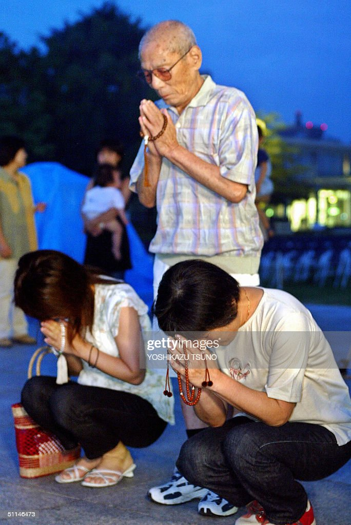 An elderly man and his family pray together in front of an altar of the memorial monument for the A-bomb victims at the peace Memorial Park in Hiroshima, western Japan 06 August 2004. The 59th memorial service for the two hundred thousand A-bomb victims was held in Hiroshima. AFP PHOTO / Yoshikazu TSUNO