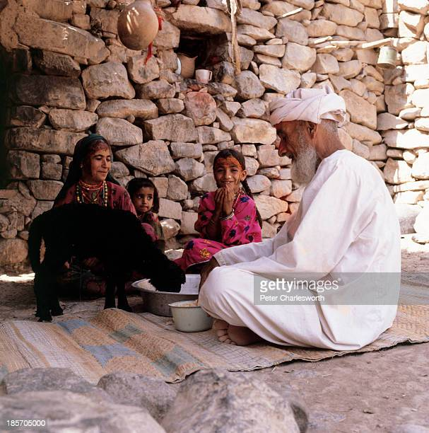 An elderly man and his wife and children sit in the shade and eat a lunch with the help of one of their goats in a small village of stone houses in...