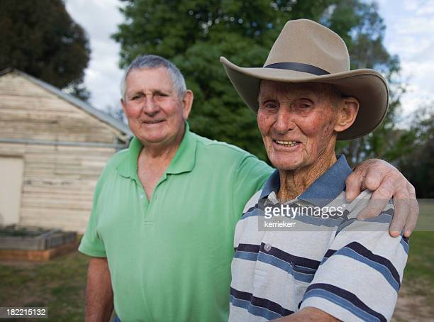 An elderly man and his younger brother standing outside