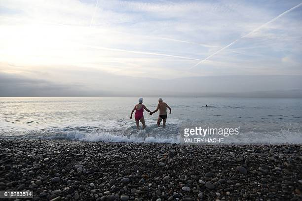 An elderly man and woman hold hands as they walk into the Mediterraneean Sea in the French riviera city of Nice on October 26 2016 / AFP / VALERY...
