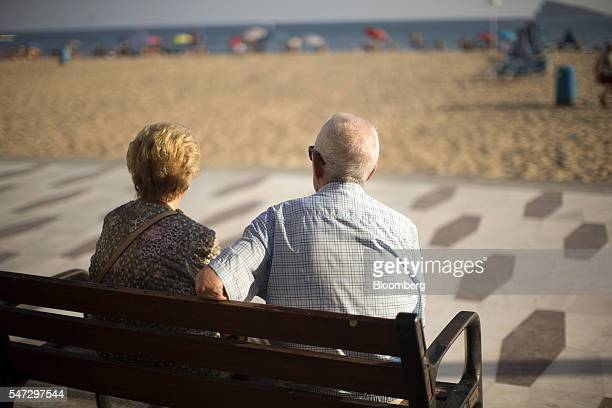 An elderly man and woman sit on a bench and look out to sea on the beachfront promenade in Benidorm Spain on Tuesday July 12 2016 Spain registered...