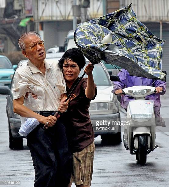 An elderly man assisted by a foreign domestic helper holds a windblown umbrella while walking on a street in Yilan a city in northeast Taiwan on...