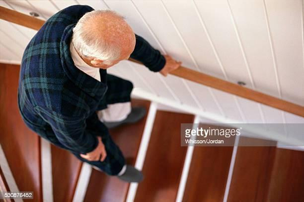 An elderly man carefully descends a staircase
