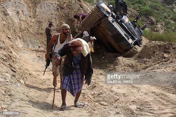 An elderly man carries a bag in front of a Yemeni tribesman from the Popular Resistance Committees -supporting forces loyal to the country's exiled...