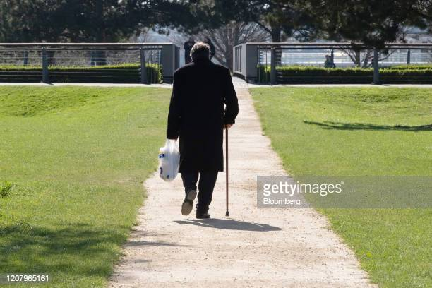 An elderly man carries his shopping in a plastic carrier bag as he walks along a pathway in the Thames Barrier Park, in London, U.K., on Sunday,...