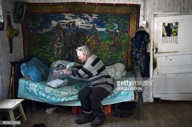 TOPSHOT An elderly man casts his ballot at his house during Russia's presidential election in the village of Buyanovo some 60 km north of Smolensk on...