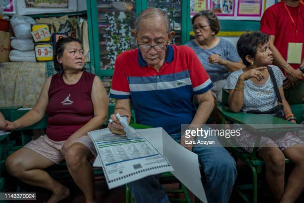 An elderly man casts his vote at a polling precinct on May 13 2019 in Manila Philippines About 60 millions of Filipino voters will head to the polls...