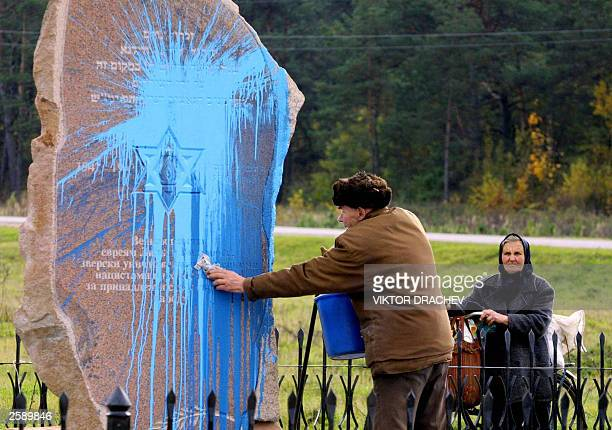 An elderly man cleans the paint poured by vandals on a Holocaust monument in Lida a town in the west of the former Soviet republic of Belarus 14...