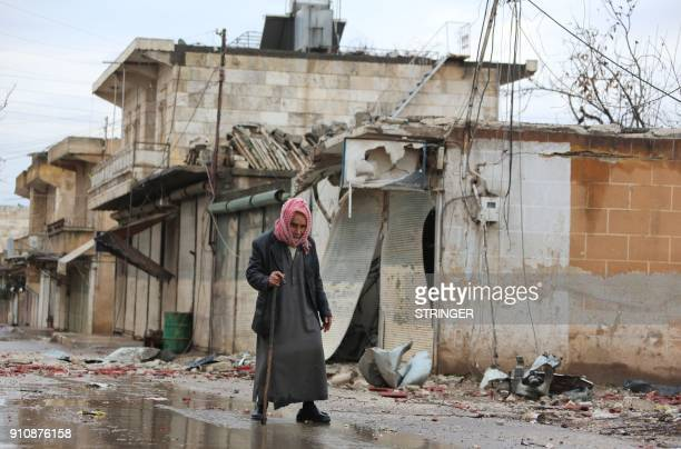 TOPSHOT An elderly man crosses a damaged street in the Kurdish town of Jandairis near the SyrianTurkish border west of the city of Afrin on January...