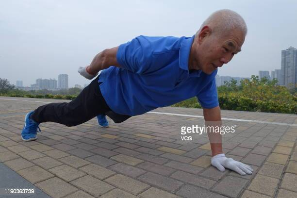 An elderly man does pushups with one hand near the Quan River on November 21 2019 in Fuyang Anhui Province of China