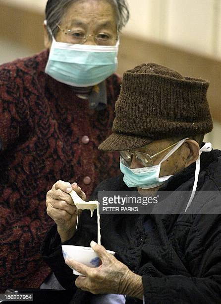 An elderly man eats his lunch in the Prince of Wales hospital wearing a mask as his wife looks on as they protect themselves against a mysterious...