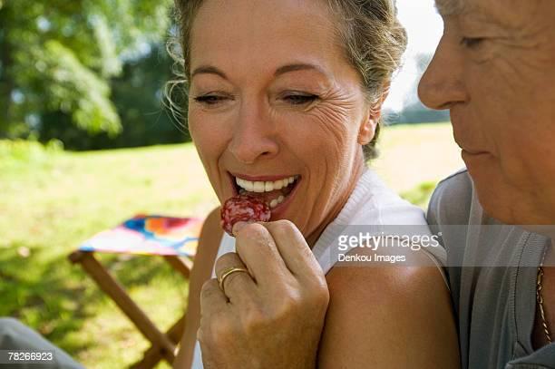 An elderly man feeding his wife.