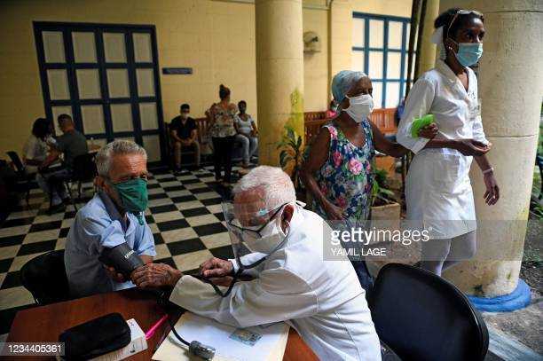 An elderly man has his blood pressure checked before being inoculated against COVID-19 with Cuban vaccine Abdala in Havana, on August 2, 2021.