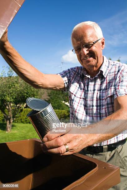 An elderly man holding a tin by a dustbin Sweden.