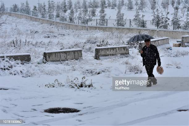 An elderly man holding an umbrella walks along a snowcovered road during a heavy snowfall in the winter season in Ankara Turkey on January 6 2019