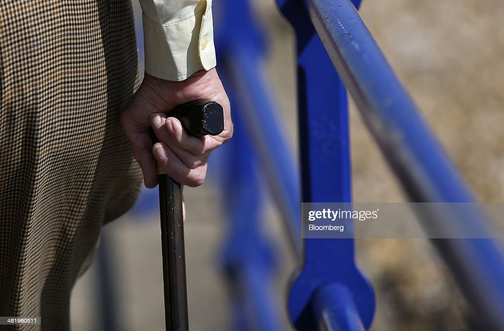 An elderly man holds a walking stick as he walks along the beachfront promenade in Eastbourne, U.K., on Tuesday, April 1, 2014. Pensioners and savers have seen returns on their money shrink since the financial crisis drove interest rates to a record low. Photographer: Chris Ratcliffe/Bloomberg via Getty Images