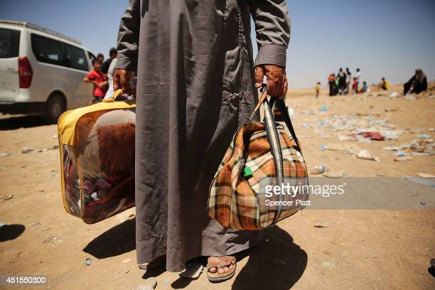 An elderly man holds his bags as over 1000 Iraqis who have fled fighting in and around the city of Mosul and Tal Afar wait at a Kurdish checkpoint in...