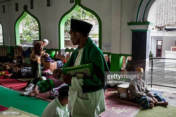 An elderly man holds the Quran at a boarding school Sepuh Payaman that cares for the elderly during Ramadan period on July 15 2014 in Magelang...