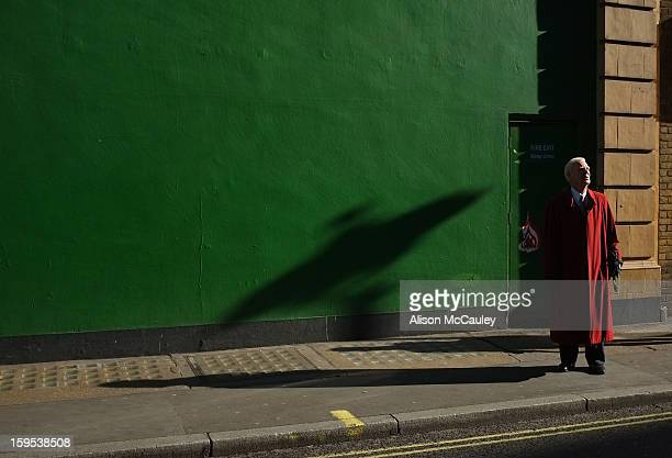 An elderly man in a long, bright red coat stands in front of a deep green wall. He looks up to the sky, which we can't see, with great curiosity. On...