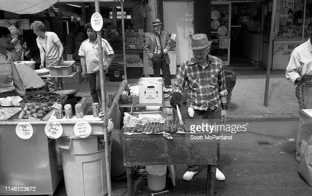An elderly man in a straw hat grills kebabs at a food vendor stall on 9th Avenue in Hell's Kitchen during the International Food Festival New York...