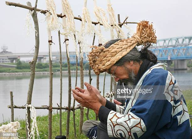 An elderly man in Ainu costume performs a ritual ancestor worshipping ceremony on a river bed in Tokyo Japan on Sunday April 8 2008 Japanese...