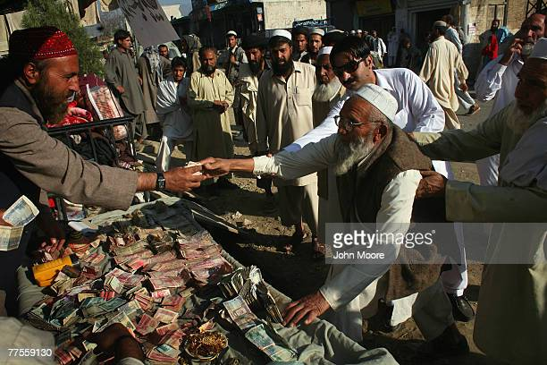 An elderly man is assisted while giving money at a donation table for militants in the village of Koza Bandi October 30 2007 in the Swat Valley...