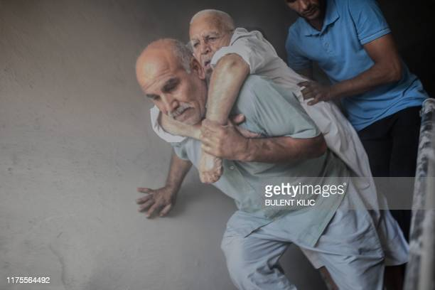 An elderly man is evacuated from a building in Akcakale, a town near the Turkish border with Syria on October 13 after it was hit by a rocket...