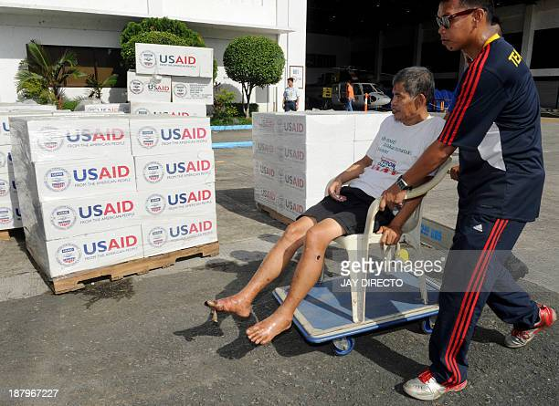 An elderly man is wheeled on an improvised wheelchair who survived the wrath of Super Typhoon Haiyan in the central coastal city of Tacloban, from a...