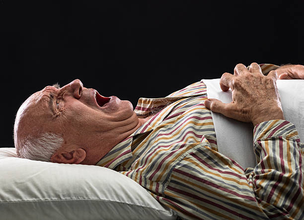 an elderly man laid in bed in severe agony - kidney stone stock pictures, royalty-free photos & images