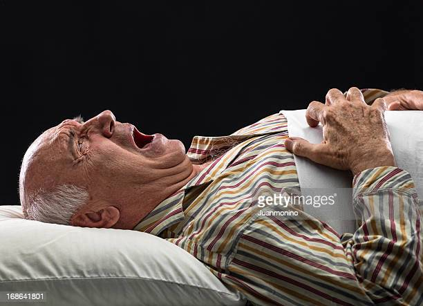 an elderly man laid in bed in severe agony