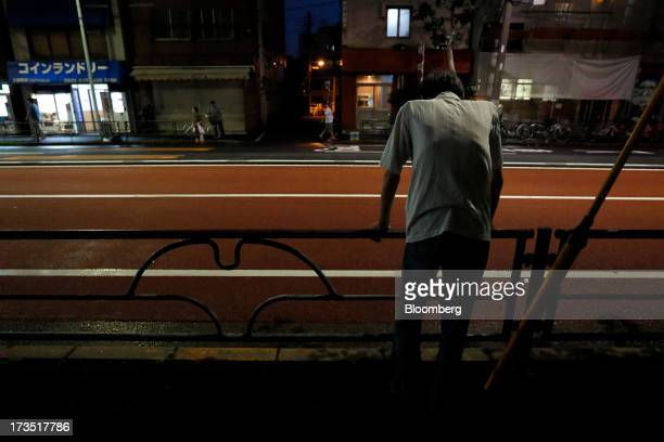 An elderly man leans on a railing along the side of a street at night in Tokyo Japan on Monday July 8 2013 The number of Japanese seniors living...