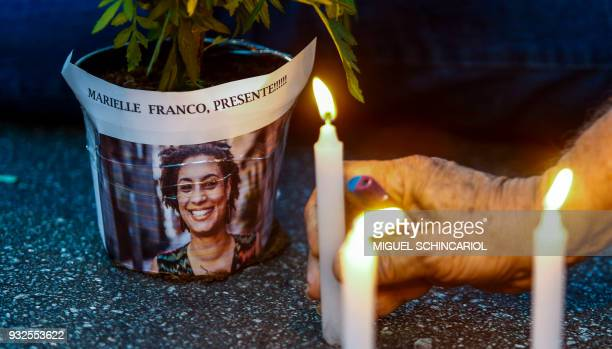 An elderly man lights a candle during a rally against the murder of Brazilian councilwoman and activist Marielle Franco in Sao Paulo Brazil on March...