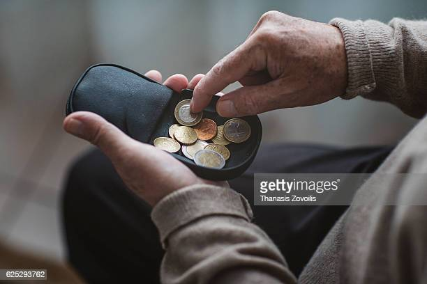 An elderly man look for some money from his wallet