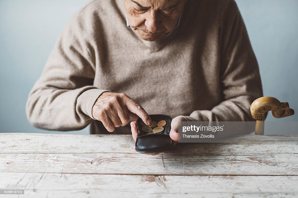 An elderly man look for some money from his wallet : ストックフォト