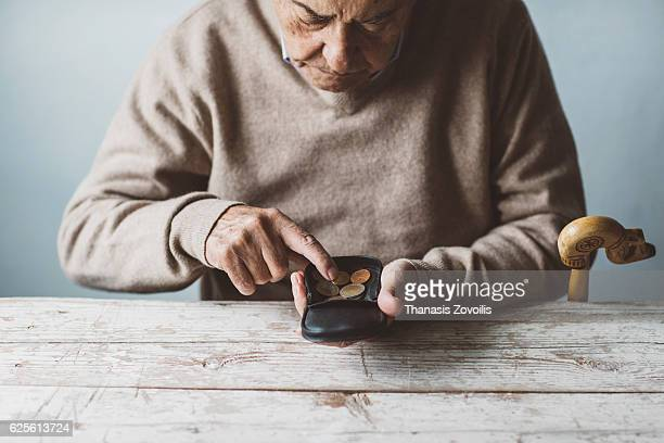 an elderly man look for some money from his wallet - armoede stockfoto's en -beelden