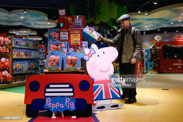 An elderly man looks at a billboard of Peppa Pig as he selects a Peppa Pig at a toy store in Beijing on January 25 2019