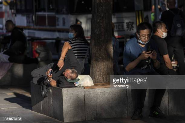 An elderly man looks at his mobile phone while resting on a bench in Beijing, China, on Wednesday, Aug. 25, 2021. China's Communist Party vowed to...