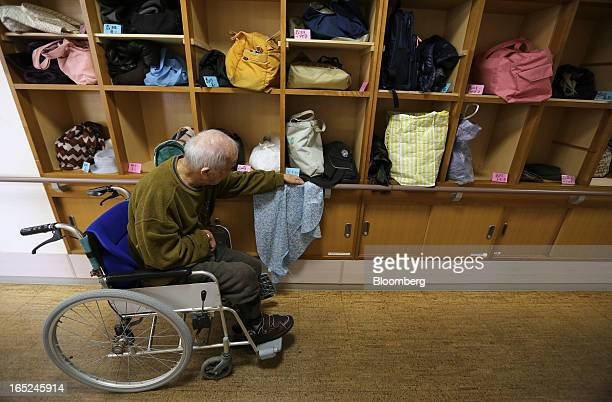 An elderly man on a wheelchair hangs an apron on a railing at a day care facility on Gogo Island in Matsuyama Ehime Prefecture Japan on Friday March...