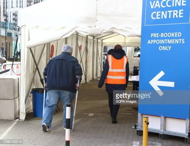 An elderly man on crutches walks into the vaccination centre A steady stream of elderly people with pre-booked appointments at the new Covid-19...