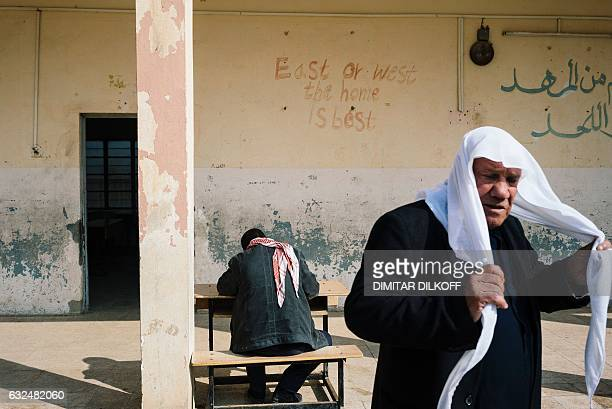 An elderly man passes by a teacher filling out school documents at a school in Mosul's eastern Gogjali neighbourhood on January 23 as scores of...