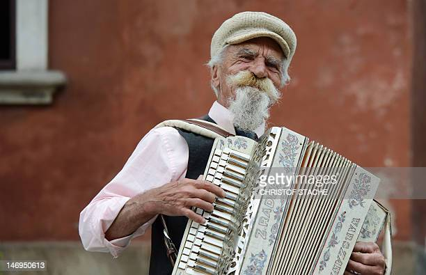 An elderly man plays his accordion at the old town market in Warsaw Poland on June 24 2012 Scores of visitors enjoy the nice weather for a...