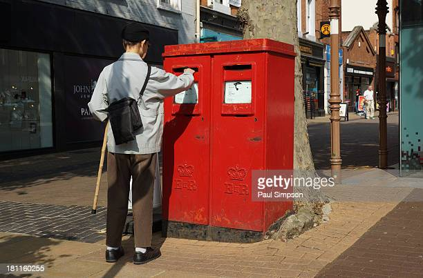 CONTENT] An elderly man posting a letter in an unusual Royal Mail post box