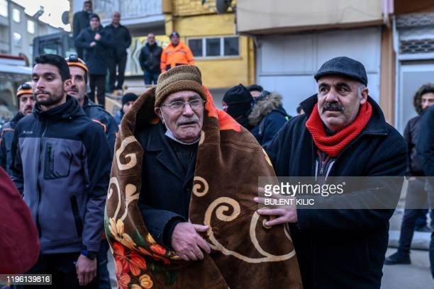 An elderly man reacts as he waits for his relatives to be saved from the rubble of a building after an earthquake in Elazig eastern Turkey on January...