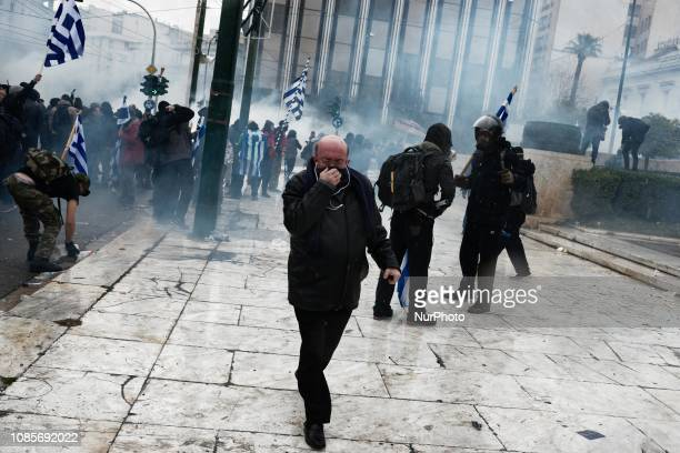 An elderly man reacts to tear gas during riots in a rally over Macedonia name row in Syntagma square central Athens on January 20 2019 Violent...