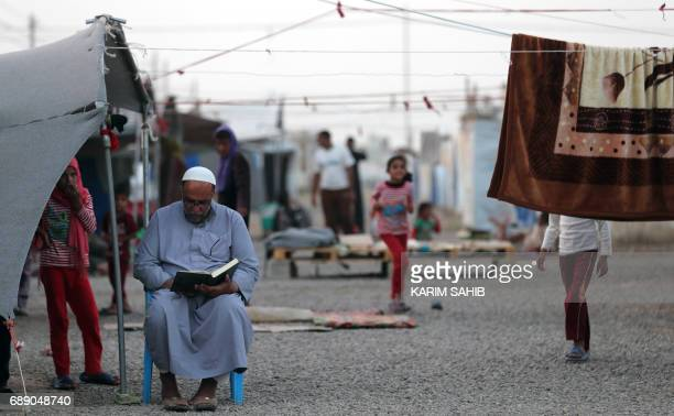 An elderly man reads the Koran Islam's holiest book on the first day of the Muslim holy month of Ramadan at alKhazir camp for the internally...