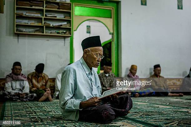An elderly man reads the Quran at a boarding school Sepuh Payaman that cares for the elderly during Ramadan on July 15 2014 in Magelang Central Java...