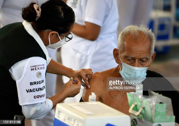 An elderly man receives a dose of the CoronaVac vaccine against COVID-19 at a vaccination center in Acapulco, Guerrero state, Mexico, on March 19,...