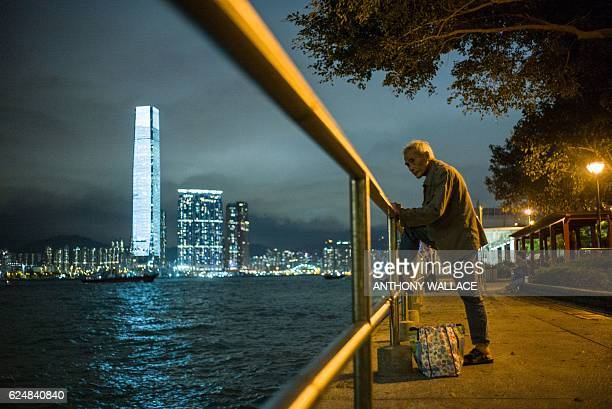 An elderly man rests his foot on a railing as he fishes in the waters of Victoria Harbour in Hong Kong on November 21 in front of a view of the...